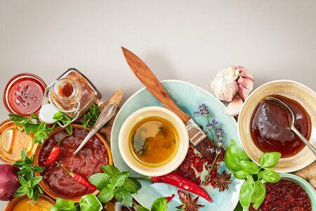 Hierbas frescas, adobos y salsas para una barbacoa de verano dispuestas como un borde inferior en blanco con espacio de copia arriba Foto de archivo