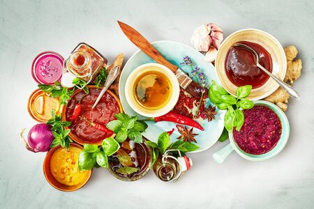 Large variety of spicy marinades and sauces with fresh ingredients and herbs on a grey background viewed from overhead Фото со стока