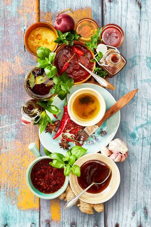 Selection of different sauces and marinades in bowls ready for a BBQ with fresh basil and herbs on a rustic multicolored wood background viewed top down Reklamní fotografie