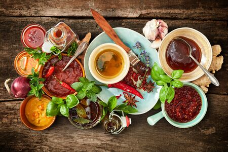 Assorted spicy marinades, sauces and rubs with fresh ingredients, herbs and spices for a summer barbecue in a food still life on rustic wood viewed from above
