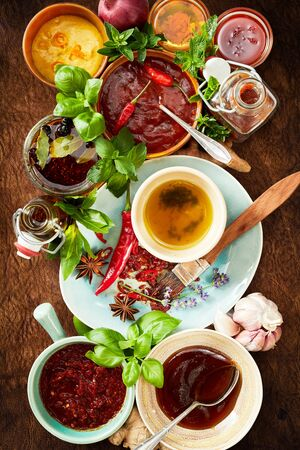 Variety of spicy, piquant and savory sauces and marinades with fresh herbs and bottles of dressing on a wood background in a top down view