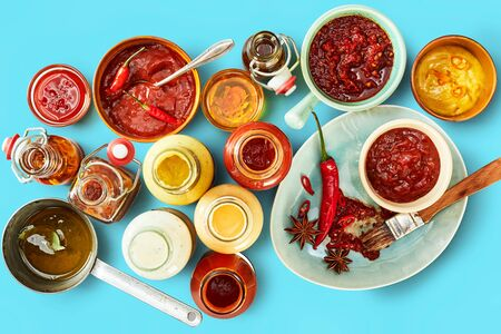 Selection of salad dressings, marinades and sauces on a colorful turquoise blue background ready for a summer BBQ