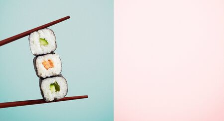 Chopsticks holding three seaweed wraps with rice and avocado over blue half of two tone background.