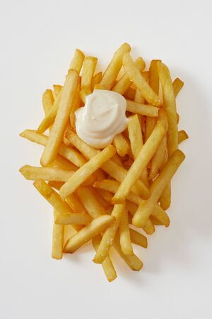 Tasty portion of golden fried potato chips, french fries with blob of mayonnaise or sour cream viewed top down on white
