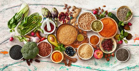 Rustic flat lay panorama of healthy fruit and vegetables with fresh produce, dried legumes and seeds and bowls of cereals viewed from above in a concept of healthy eating