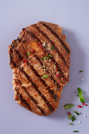 Portion of lean tender marinated grilled beef steak seasoned with fresh herbs, spices and salt on a blue grey background viewed from above