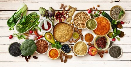 Panorama banner healthy vegetarian diet concept with a large assortment of fresh vegetables, fruit, seeds, pulses, legumes and spices on a white painted wooden table Reklamní fotografie