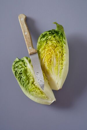 Sharp wet kitchen paring knife with a sliced head of Chinese or Napa cabbage showing the crinkly leaves on a grey background Stock Photo
