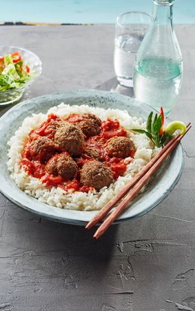 A bowl of meatballs with red spicy sauce and white rice