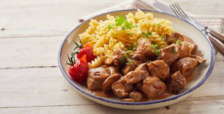 Spiral fusilli pasta dish with diced pork and tomatoes in bowl  on wooden table