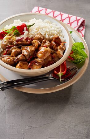 A bowl of rice, diced chicken, peppers and basil on table