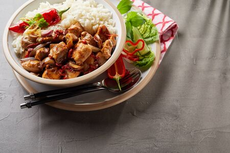 A bowl of rice with meat and assorted vegetables over grey background Reklamní fotografie