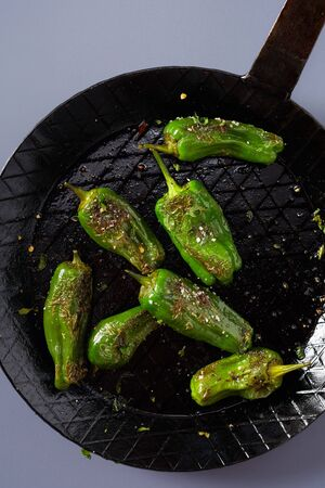 Spicy seasoned roasted whole green jalapeno chili peppers in a vintage skillet or frying pan