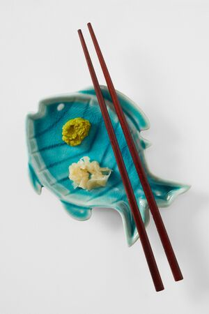 Fresh wasabi and gingers on blue ceramic fish dish with chopsticks Stock Photo