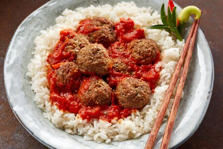 A bowl of white rice and beef meatballs with red sauce, closeup