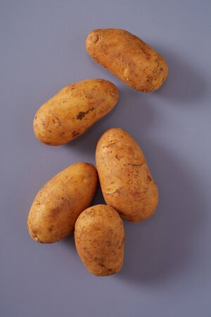 Fresh raw whole potatoes on grey background