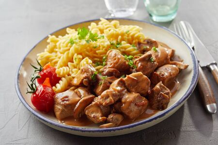 Seasoned spiral pasta and diced goulash with gravy