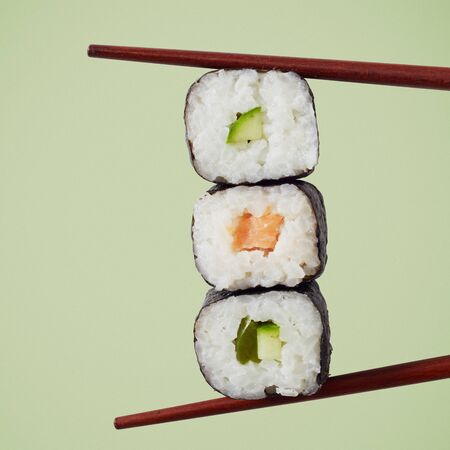 Three maki sushi rolls with nori seaweed, rice, salmon and avocado pear with chopsticks over a square green background
