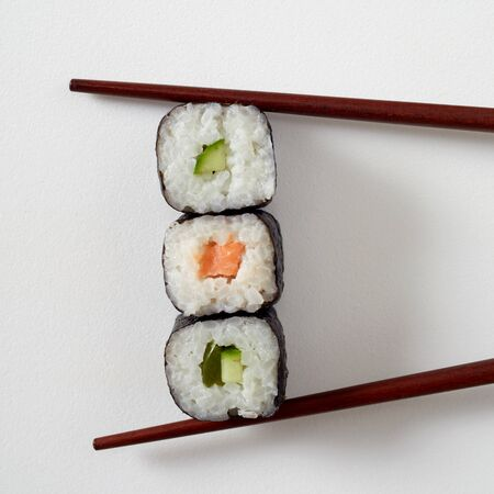 Food styling concept with three maki sushi rolls with nori seaweed, salmon and avocado pear placed between bamboo chopsticks on white