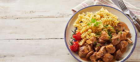 Tasty fusilli pasta and sliced meat with gravy in bowl on  rustic wood plank table.