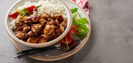 A bowl of white rice and diced meat with sauce on grey background