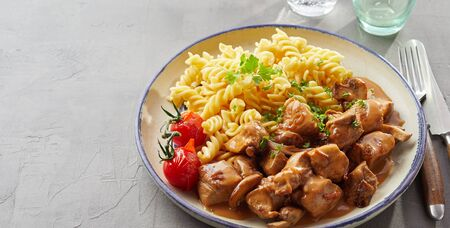 A plate of spiral pasta and spicy beef on grey background Zdjęcie Seryjne