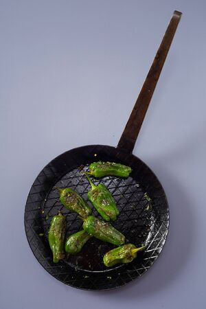 Skillet with roasted or grilled green Jalapeno chili peppers seasoned with spices, herbs and salt viewed from overhead on grey with copy space Reklamní fotografie