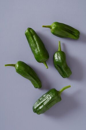 Five fresh spicy green jalapeno chili peppers  on a grey background Stock Photo
