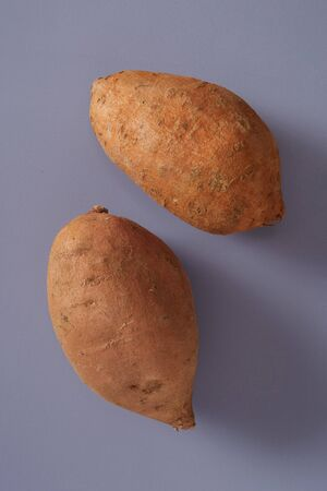 Two whole fresh cleaned sweet potatoes or yams in a close-up view on a grey background