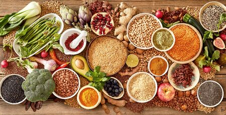 Bowls of assorted cereals, legumes and seeds with fresh vegetables and fruit in a close-up top down panorama view conceptual of a healthy diet or vegetarian cuisine