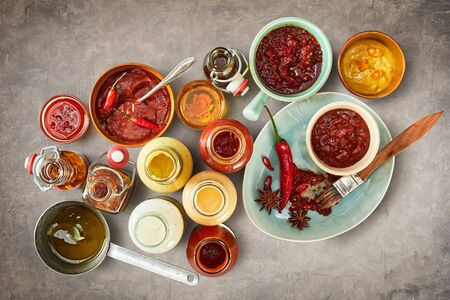 Assorted sauces, marinades and dressings on a textured grey slate background