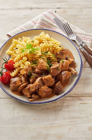 Overhead view of bowl holding delicious pasta and tender sliced veal chunks over rustic wood background