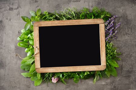 Small slate surrounded by an assortment of fresh herbs and edible flowers with copy space on textured grey background