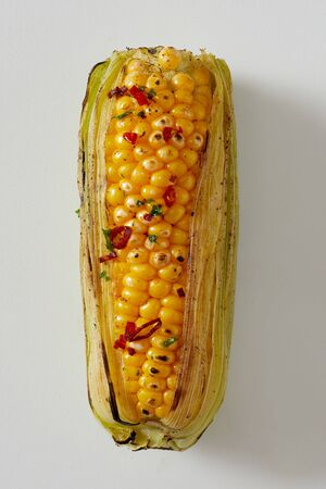 Fresh spicy grilled corn on the cob seasoned with red chili pepper in a close up view with outer leaves on white