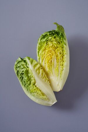 Halved Chinese cabbage showing wrinkled leaves on grey background