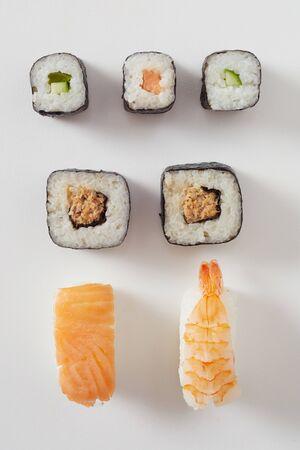 Assorted fresh sushi arranged on white with raw salmon nigiri, prawn or lobster sashimi and maki rolls with nori seaweed Фото со стока