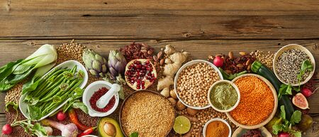 Rustic panorama of fresh healthy vegetables and fruit, dried pulses and seeds on a wooden background with copy space Stock fotó