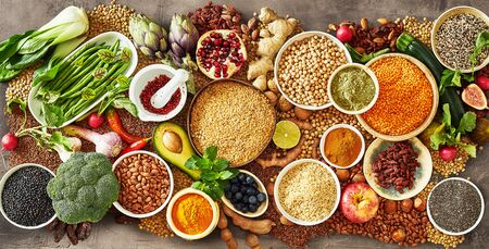 Colorful array of healthy fruit and vegetables with fresh produce, dried legumes, cereals and seeds and assorted herbs and spices in a panorama banner for vegetarian cuisine