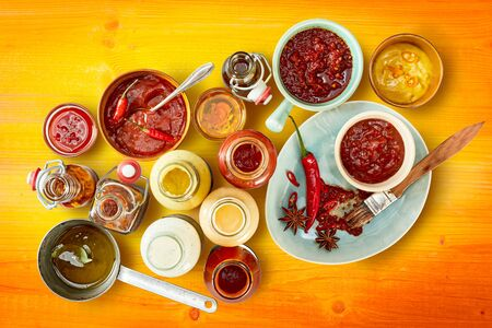 Assorted sauces, dressings and marinades with spices  on colorful orange stained yellow wood background