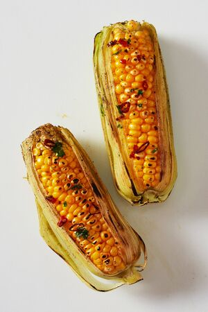 Spicy grilled corn on the cob seasoned with chili from a summer barbecue viewed from above on white in a healthy diet and seasonal cuisine concept