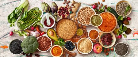 Panorama of fresh fruit and vegetables with bowls of legumes, cereals and seeds for a healthy diet  on white wood table Stock fotó