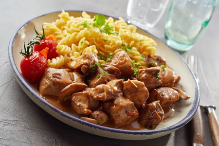 A plate of scrumptious fusilli pasta, whole tomatoes and seasoned pork chunks with sauce