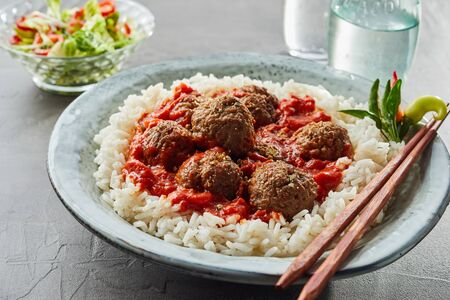 Scrumptious rice with meatballs and sauce in white bowl Reklamní fotografie