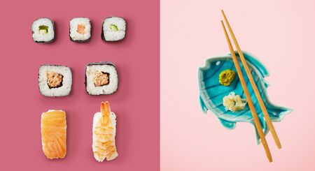 Sushi and avocado rice rolls next to fish plate holding chopsticks and green wasabi sauce over two tone pink background