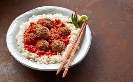 A bowl of white rice with spicy meatballs in sauce.