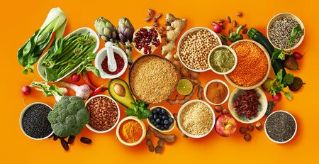 Fresh and dried produce with vegetables, fruit, seeds, pulses, spices and herbs on orange color background