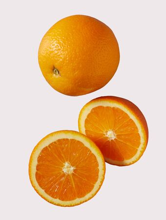 Whole and halved juicy fresh summer orange rich in vitamin C isolated on white in a healthy diet concept