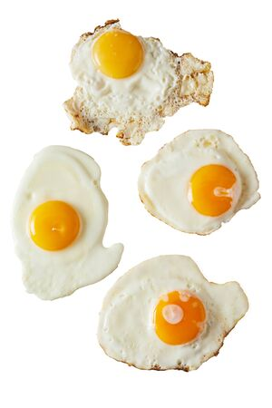 Four fried eggs ranging from soft to crispy with bright yellow yolks isolated on white viewed from above for food placement or menu advertising