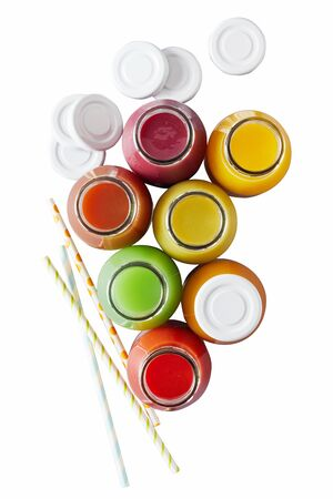 Overhead view on assorted different colored bottles of juice next to white caps and straws on isolated white