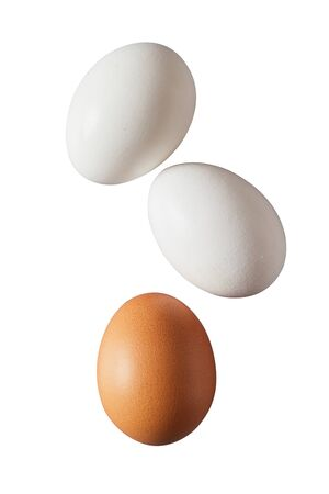 Three whole raw or hard boiled brown and white fresh hens eggs in their eggshells isolated on white Фото со стока